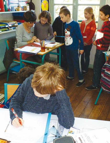 Les élèves qui ont achevé leur tâche en autonomie viennent faire vérifier leur travail par l'enseignante.