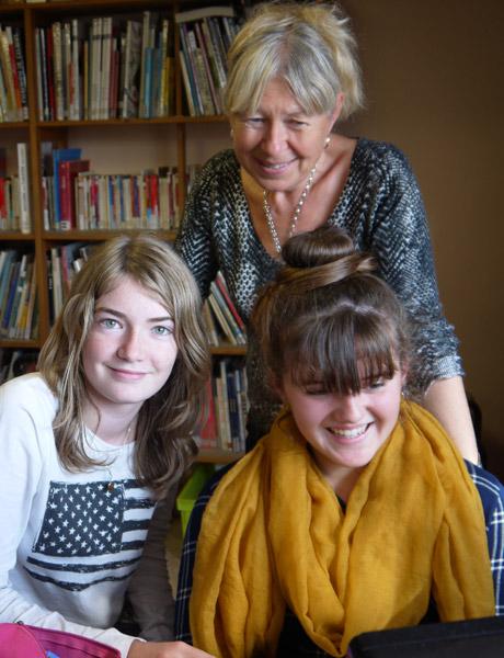 Trois collégiennes relisant des articles. Derrière : la documentaliste du collège, Joëlle Roux.