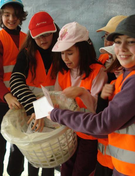 Les enfants inspectent les poubelles pour voir si le tri a bien été fait.